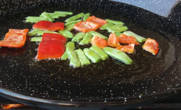 Vegetables sauteing in meat paella